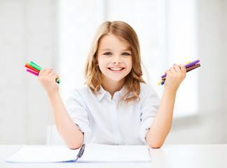 smiling girl showing colorful felt-tip pens