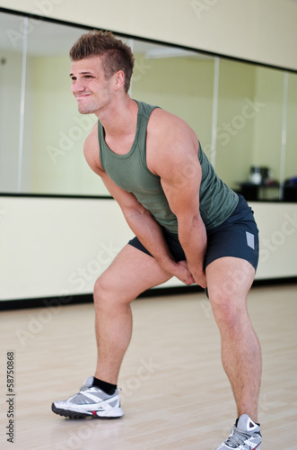 Handsome young man working out in gym with kettlebell