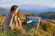 Young artist painting an autumn landscape