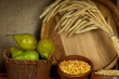 Pears in basket and bowls of grains with wooden tub