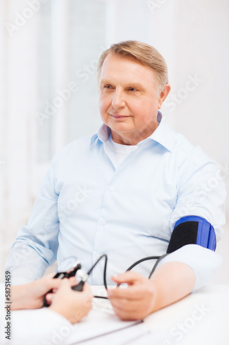 female doctor or nurse measuring blood pressure