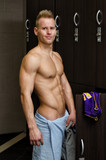 Shirtless young male athlete in gym dressing room with towel