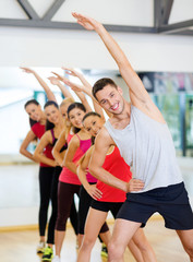 group of smiling people stretching in the gym