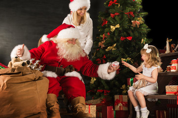 Photo of cute girl and her mother and Santa Claus at home near C