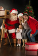 Santa Claus taking picture of full family with old wooden camera