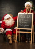 Santa Claus with his helper standing near chalkboard with wishli