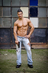 Shirtless, muscular latino young man holding gun