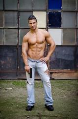 Shirtless, muscular latino young man holding gun