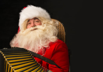 Santa Claus sitting in armchair at home and playing music on acc