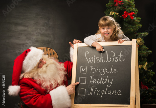 Santa Claus with child sitting near chalkboard with wish list an