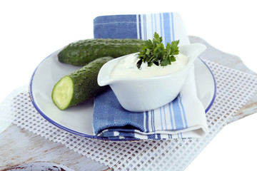 Cucumber yogurt in sauceboat, on color napkin, isolated on