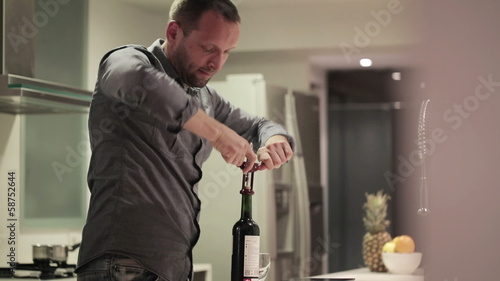 Young handsome man opening bottle with wine in kitchen