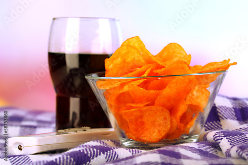 Chips in bowl, cola and TV remote on plaid on bright background