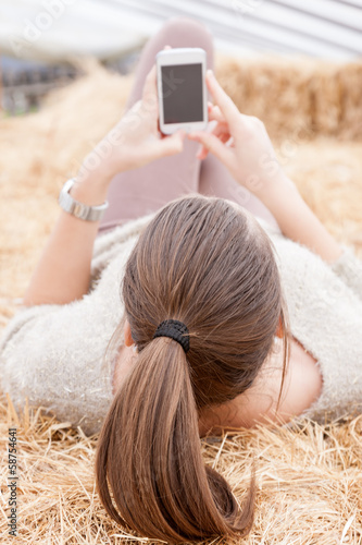 Brunette teen girl sending a text lying on a haystacks