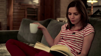Young pretty woman reading book, drinking tea in home