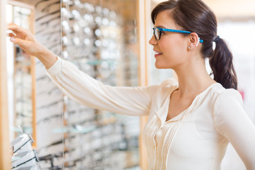 Woman Buying Glasses At Optician Store