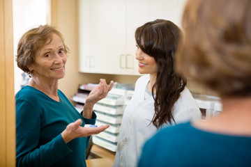 Optometrist Looking At Woman Holding Contact Lens