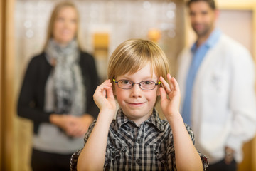 Boy Trying Glasses With Optometrist And Mother At Store