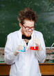 Mad professor laughs keeping two flasks with colored liquid