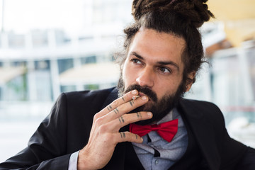 Stylish elegant dreadlocks businessman smoking