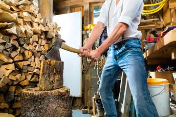 Junger Mann hackt Feuerholz in den Bergen