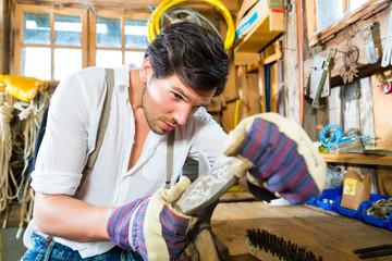 Junger Mann schleift sein Werkzeug in Bergen