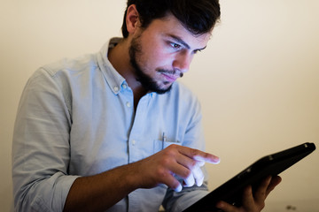 young man using and illuminated by the light of tablet