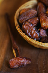 Dates, dried preserved sweet fruits with a wooden fork, serving