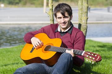 mann übt draußen gitarre spielen