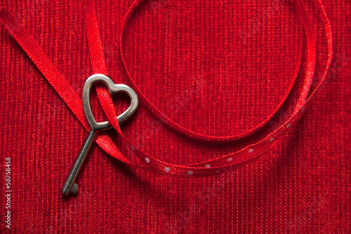 Heart shaped key with a red ribbon on red velvet