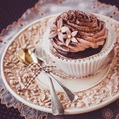 Beautiful chocolate cupcake on vintage plate.