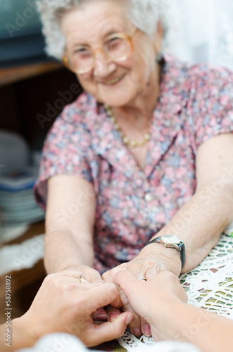 canvas print picture Young hand holding an elderly pair of hands