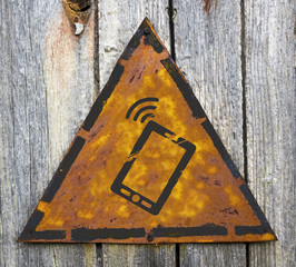 Smartphone Icon on Rusty Warning Sign.