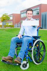 Rollstuhlfahrer zeigt weißes Schild