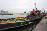 Tugboat and fishing vessels are at berth in the port of Macao.
