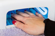 Hands with uv lamp for nails
