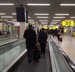 Travellers on a moving walkway in an airport