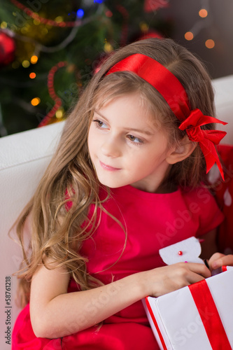 Adorable curly girl with Christmas present