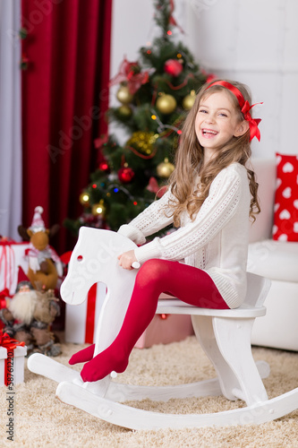 Happy girl playing  in Christmas decorated room