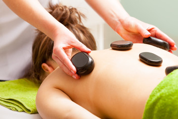 Spa salon. Woman relaxing having hot stone massage. Bodycare.