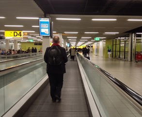 Traveller on a moving walkway in an airport