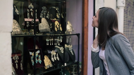 Elegant woman looking at beautiful jewellery on shopwindow