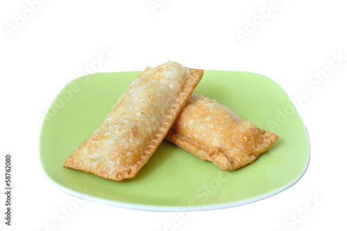 Crispy pies on green plate isolated white background.
