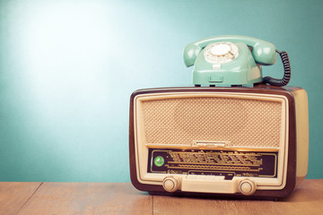 Retro old radio and mint green telephone on wooden table