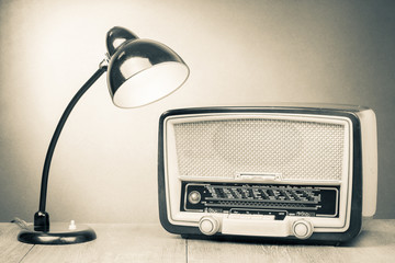 Retro old desk lamp and radio on table sepia photography