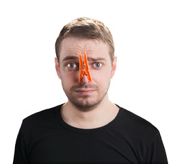 Man with clothespin on his nose - bad smell concept photography.