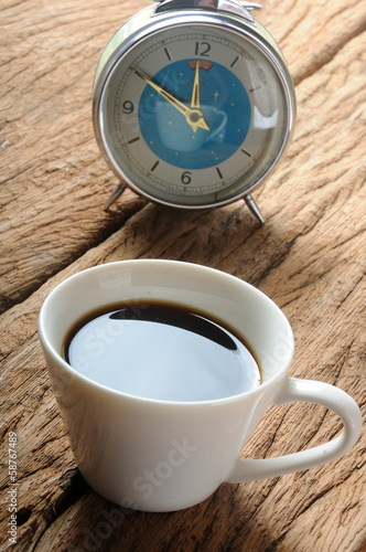 a cup of coffee with its reflection on glass of clock
