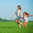 Young happy girls running at green wheat field