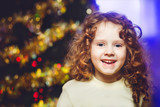 Little curly girl near the Christmas tree, smiling