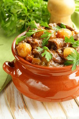 Beef stew with vegetables and herbs in a clay pot